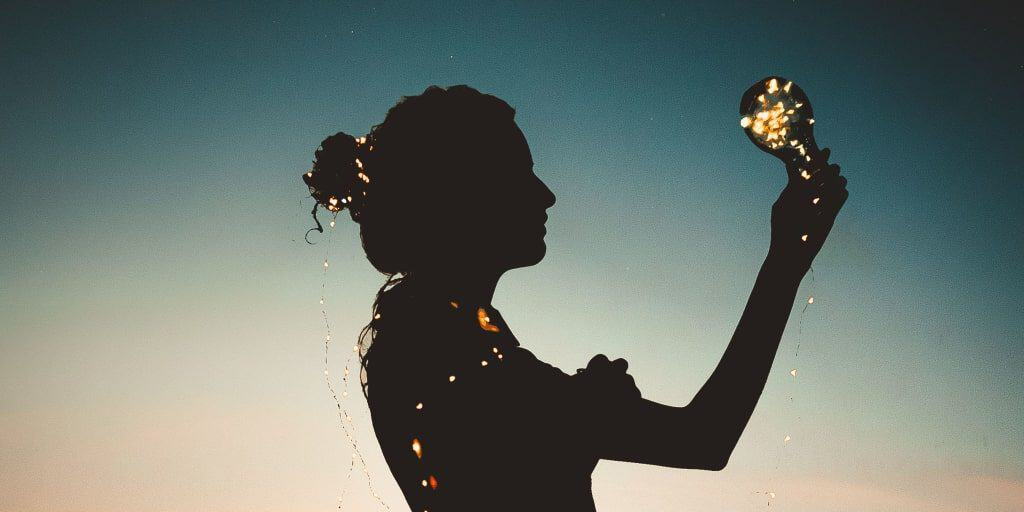 silhouette of a woman holding a lighted bulb simulating looking at new ideas and change