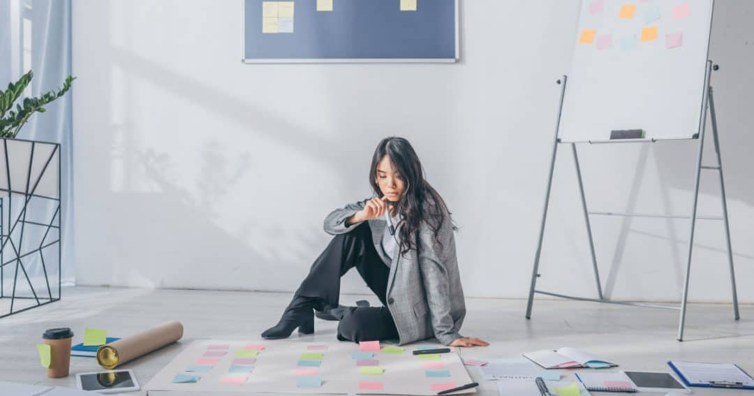 woman sitting on floor with planning notes all around her